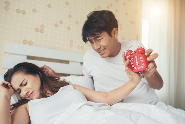 Paar dat problemen met het opstaan vroeg in de ochtend op het bed heeft