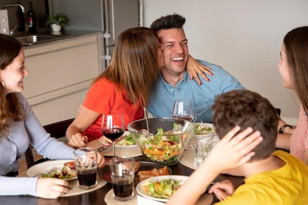 Paar dat romantisch is tijdens het familiediner