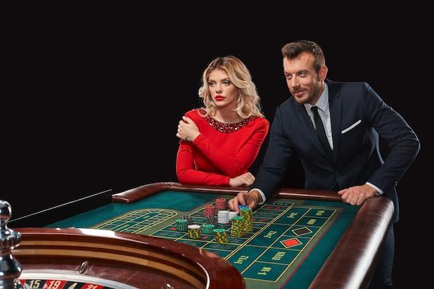 Paar dat roulette speelt wint in het casino. verslaving aan het gokken. hij zet chips in