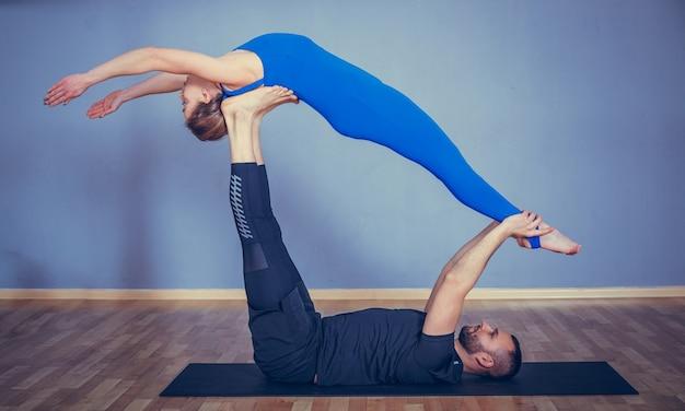 Paar dat samen acroyoga beoefent. paar beoefenen van acro yoga in een witte studio.