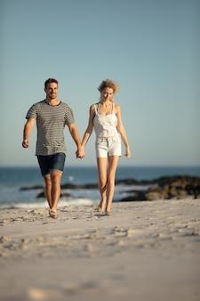 Paar dat samen hand in hand op het strand loopt