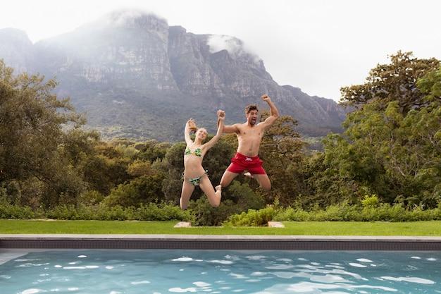 Paar dat samen in het zwembad springt