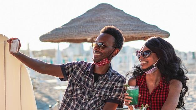 Paar dat selfie met gezichtsmasker in strandbar neemt
