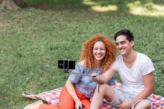Paar dat selfies met slimme telefoon neemt op picknickdatum
