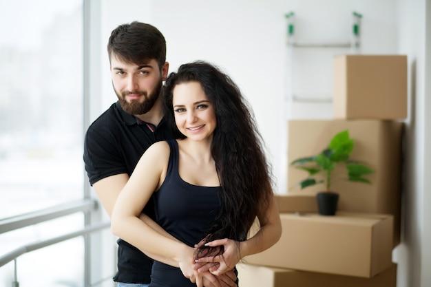 Paar dat sleutels toont tot het nieuwe huis koesteren die camera bekijkt