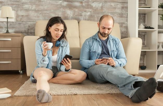 Paar dat smartphone gebruikt terwijl ze op het vloerkleed in de woonkamer zitten