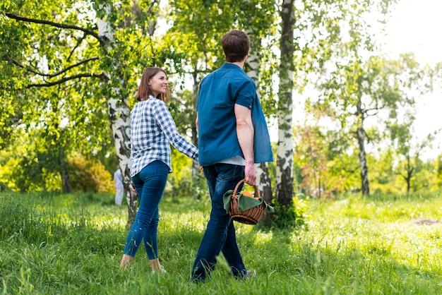 Paar dat terwijl het gaan voor picknick in bos glimlacht