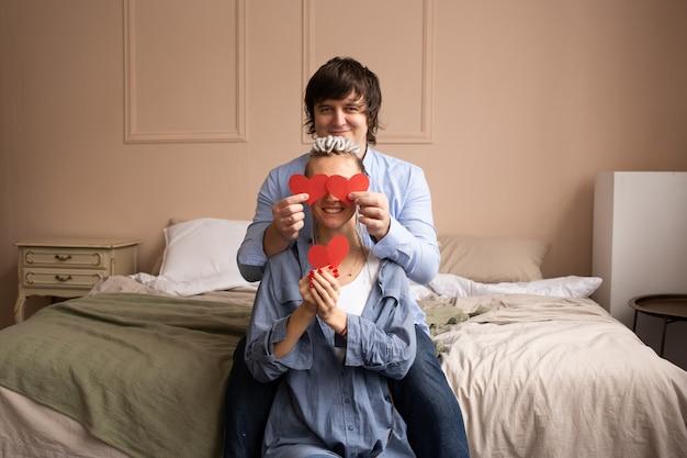 Paar dat thuis met elkaar met rood hartvalentijnskaart speelt in handen.