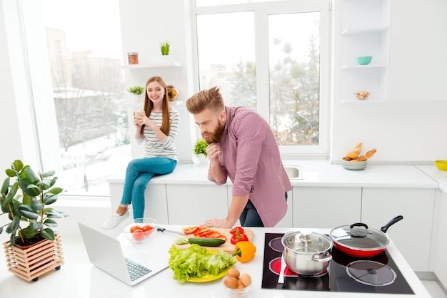 Paar dat thuis samen in de keuken met laptop zit