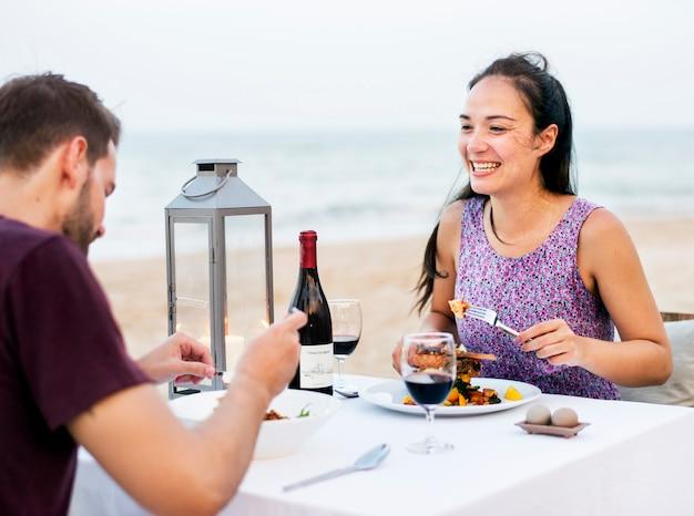 Paar dat van een romantisch diner geniet bij het strand