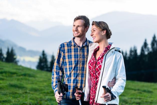 Paar dat van mening geniet die in de alpiene bergen wandelt