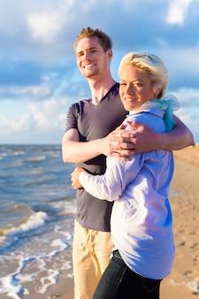 Paar dat van romantische zonsondergang op strand geniet