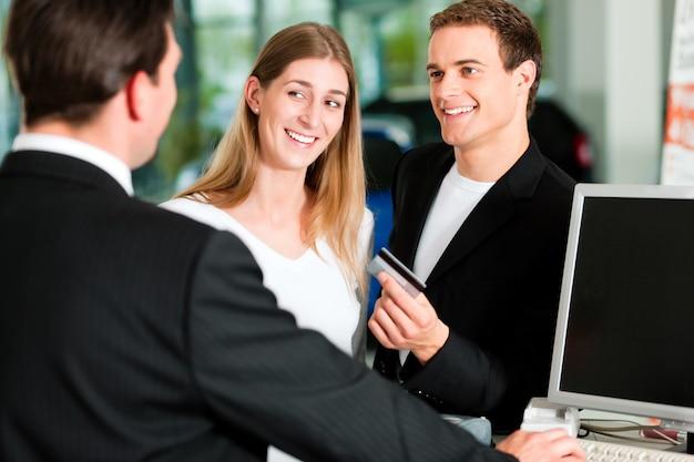Paar dat verkoopcontract ondertekent bij autohandelaar