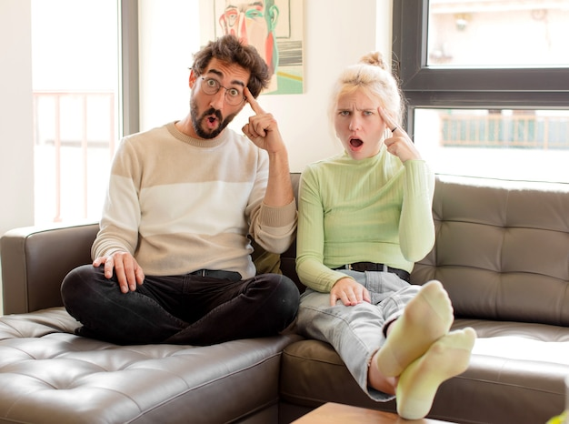 Paar dat verrast, met open mond, geschokt kijkt en een nieuwe gedachte, idee of concept realiseert