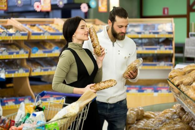Paar dat verse gebakjes kiest bij supermarkt