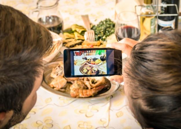 Paar dat voedselfoto met mobiele slimme telefoon neemt bij restaurant