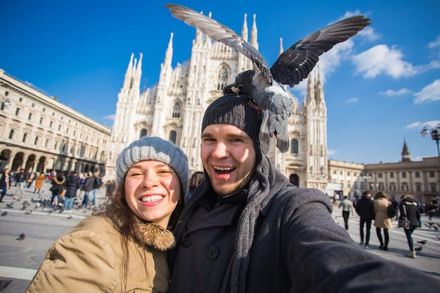 Paar dat zelfportret met duif in duomo-vierkant in milaan neemt.