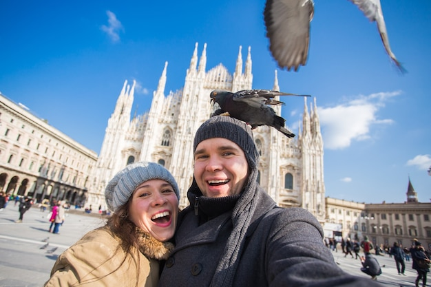 Paar dat zelfportret met duif neemt op het duomo-plein in milaan. winterreizen, italië en relatieconcept