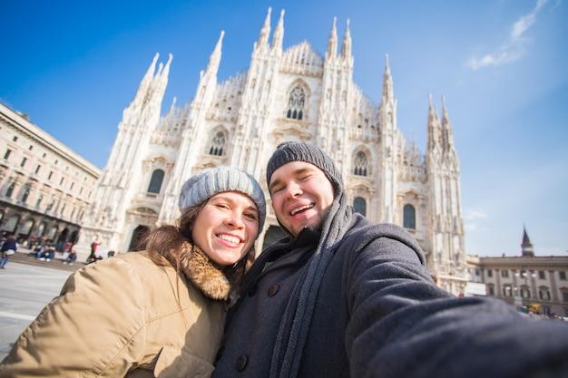 Paar dat zelfportret neemt op het duomo-plein in milaan. reizen en relatie concept