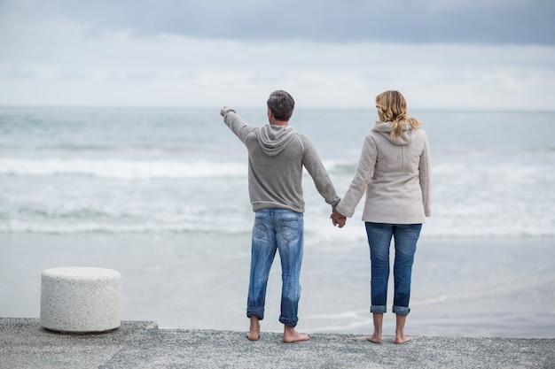Paar dat zich met holdingshanden op het strand bevindt