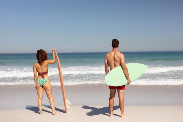 Paar dat zich met surfplank op strand in de zonneschijn bevindt
