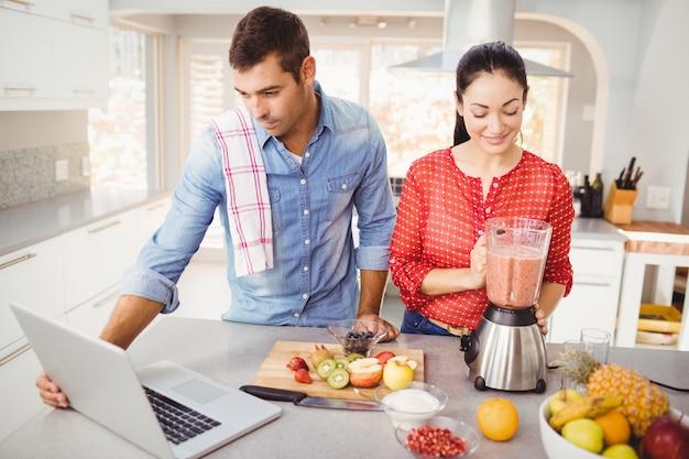 Paar dat zich met vruchtensap bevindt terwijl mens die laptop met behulp van