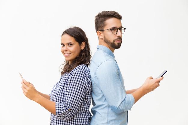 Paar dat zich rijtjes bevindt en mobiele telefoons gebruikt