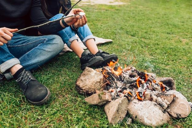 Paar dichtbij het kampvuur die marshmallows roosteren