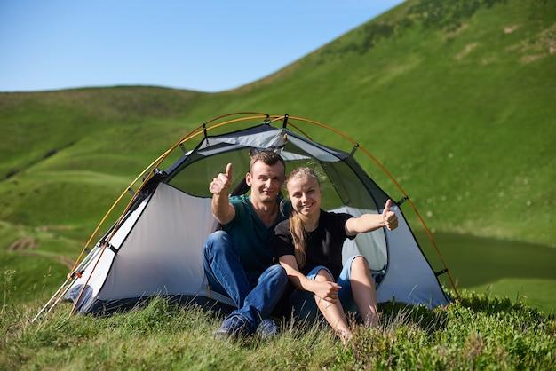 Paar dichtbij toerist met tent die in de bergen genieten