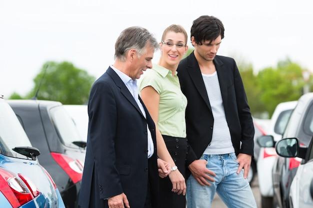Paar die auto op werf van handelaar bekijken