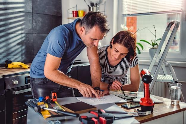 Paar die blauwdrukken tijdens keukenvernieuwing bekijken