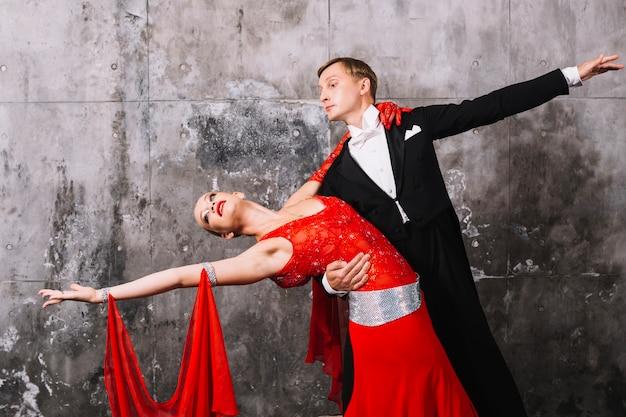 Paar die dans uitvoeren dichtbij grijze muur