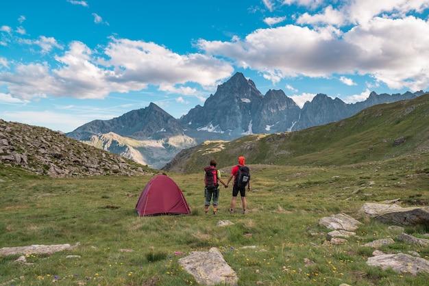 Paar die de majestueuze mening van gloeiende bergpieken bekijken bij zonsondergang hoog omhoog op de alpen