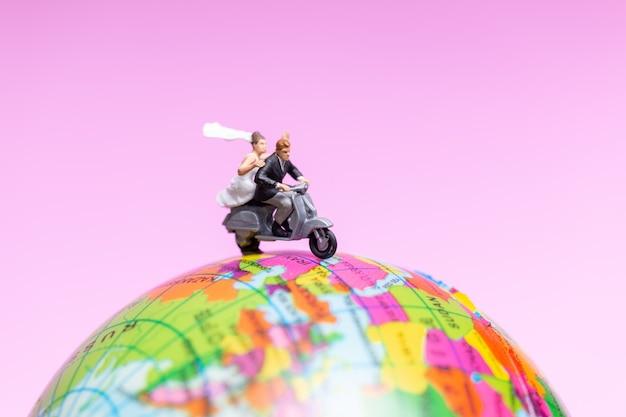 Paar die de motorfiets berijden op de bol, valentijnskaartenconcept