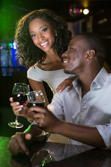 Paar die en hun wijnglazen glimlachen roosteren bij barteller in bar