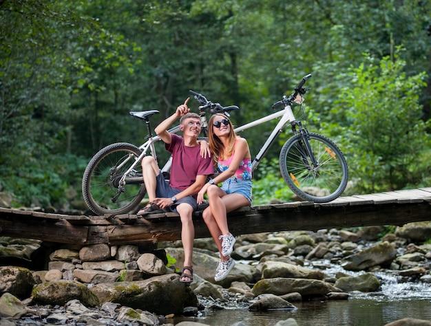 Paar die in het bos op rivierbrug rusten dichtbij fietsen