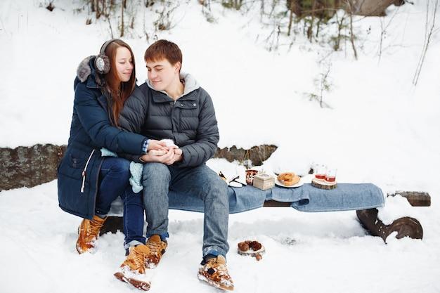 Paar die in liefde hete thee buiten in de winter drinken