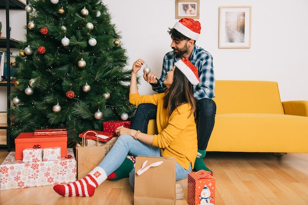 Paar die kerstmisboom in woonkamer verfraaien