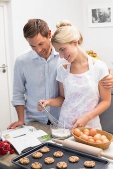 Paar die kokboek bekijken en koekjes in keuken voorbereiden