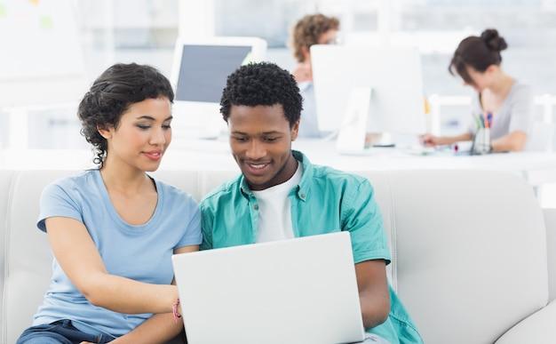 Paar die laptop met collega's met behulp van op creatief kantoor