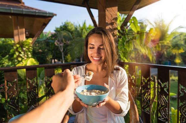 Paar die ontbijt hebben samen oogpunt van man die jonge vrouw voeden