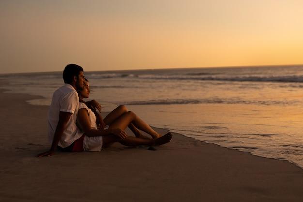 Paar die op zee op het strand tijdens zonsondergang kijken