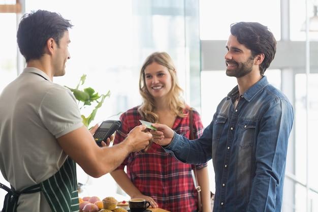 Paar die rekening betalen bij koffiewinkel die kaartrekening gebruiken