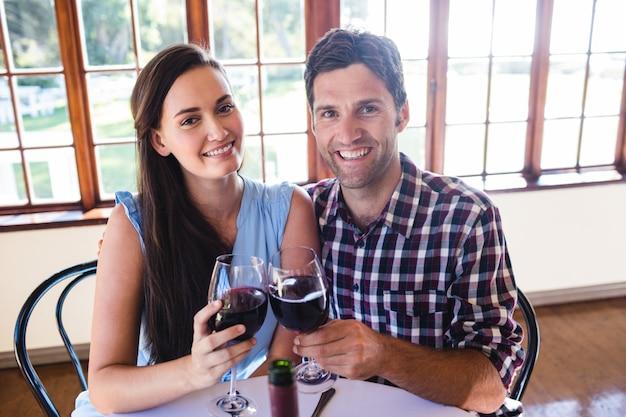 Paar die rode wijnglas in restaurant roosteren