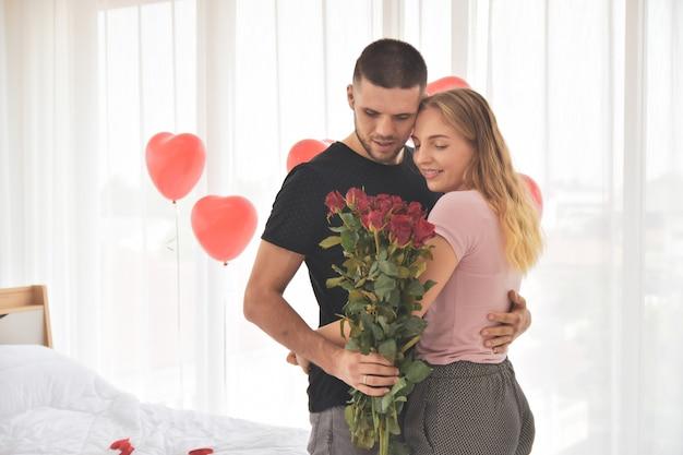 Paar die roze bloem in slaapkamergeluk geven in de dag selectieve nadruk van de valentijnskaart