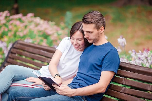 Paar die tablet en cellphone in openbaar park gebruiken.