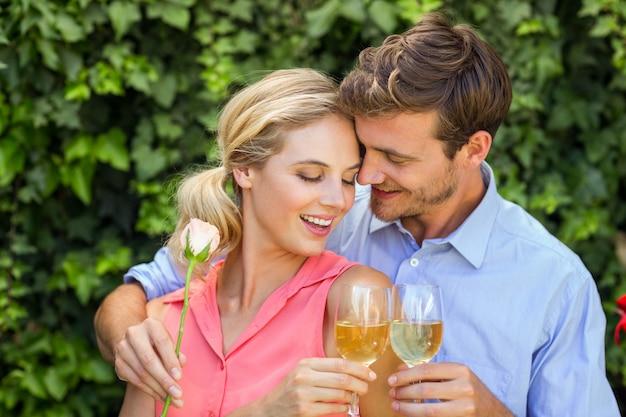 Paar die terwijl het roosteren van wijnglazen bij voortuin omhelzen