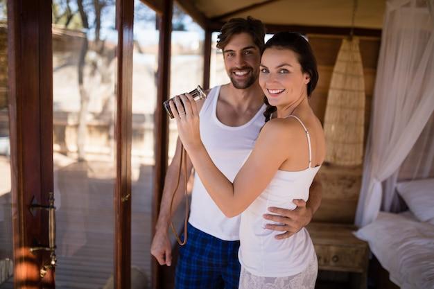 Paar die trogverrekijkers van venster tijdens safarivakantie kijken
