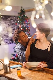 Paar die tussen verschillende rassen ontbijt op kerstavond hebben. duizendjarige jong koppel liefde concept.