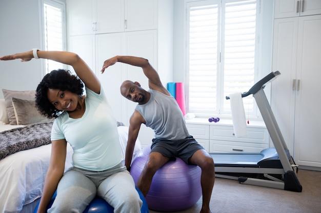 Paar die uitrekkende oefening op geschiktheidsbal uitvoeren in slaapkamer